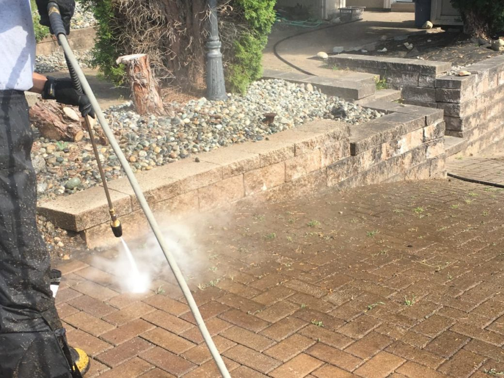 A man pressure washing the ground